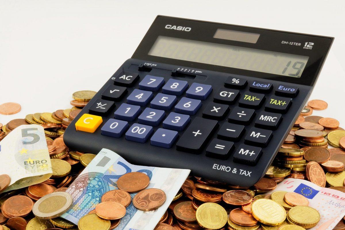 Taschenrechner liegt auf Geldmünzen und -scheinen