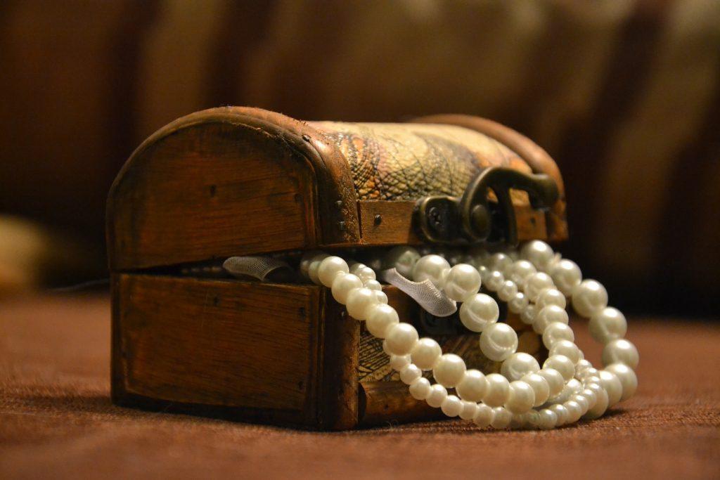 Perlenketten, die aus einem Schatzkoffer kucken