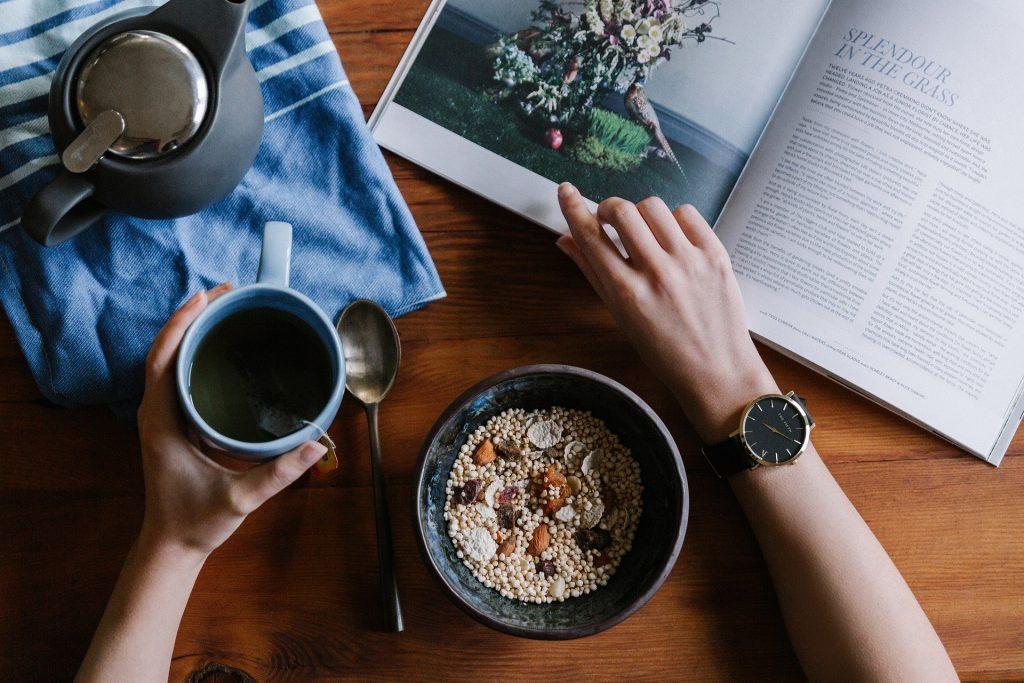 Müsli und Kaffee, dabei ein aufgeschlagenes Buch, in dem eine Hand blättert