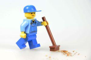 Legomännchen mit braunem Besen fegt Krümmel von weißer Oberfläche