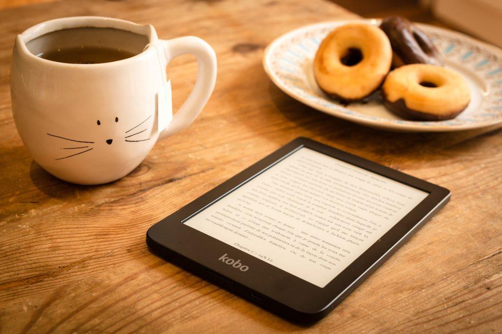 E-Reader auf Holztisch, Teller mit Donuts und Teetasse