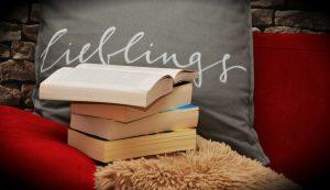 """Graues Kissen, auf dem """"Lieblings"""" steht, davor ein Stapel Lieblingsbücher"""