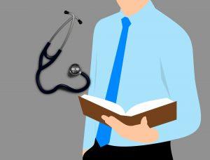 Zeichnung: Oberkörper im hellblauen Hemd mit Krawatte hält Buch in der Hand, Stethoskop